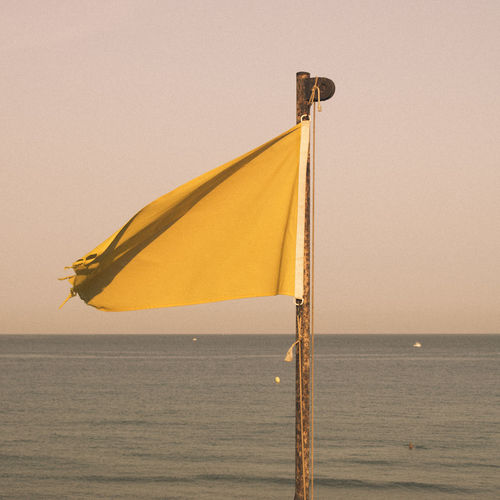 Yellow flag on pole by sea against clear sky