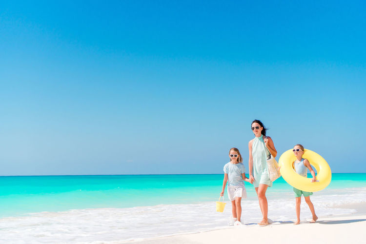 Mother and daughters walking on beach