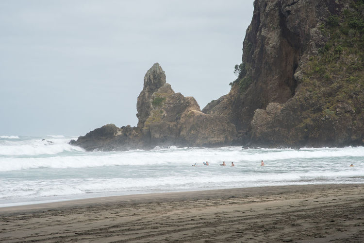 Auckland, New Zealand-December 17,2016: Stunning black sand Piha Beach, volcanic rock and tourists swimming in the powerful Tasman Sea waves in Auckland, New Zealand Auckland Flowing Water Lion Rock Swimming Tasman Sea Beach Beauty In Nature Black Horizon Over Water Motion Nature New Zealand Piha Power In Nature Rock Rock - Object Rock Formation Sand Scenics - Nature Sea Solid Travel Destinations Volcanic Landscape Volcano Wave