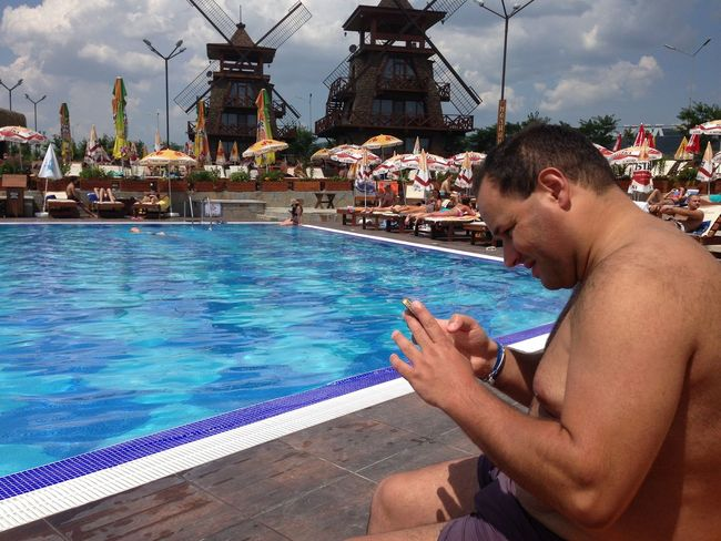 Happy Leisure Activity Lifestyles Man Outdoors Person PhonePhotography Sitting Sky Smartphone Swimming Pool Texting Travel Water