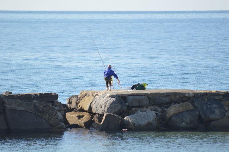 People fishing in sea against sky
