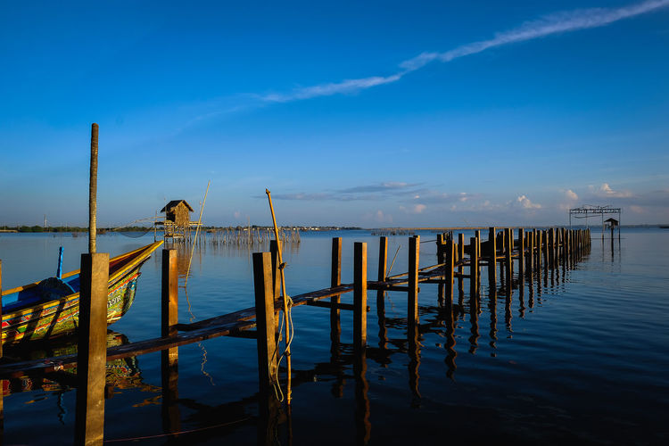 Wooden posts on pier over lake against sky