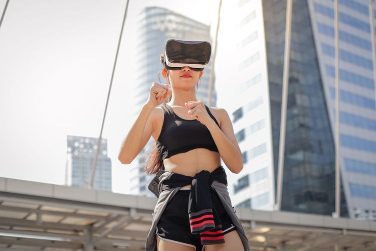 Young woman using virtual reality simulator standing against building in city