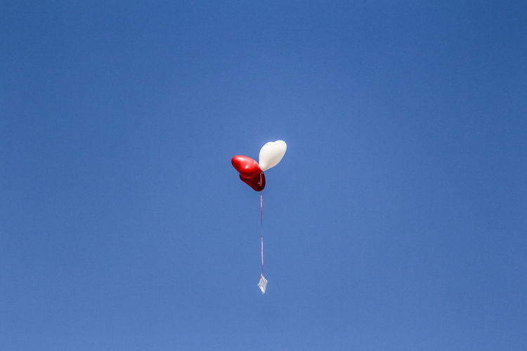 Three Heart Shape Balloons In Air Against Clear Sky