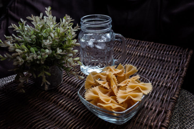 Farfalle Pasta And Drinking Water On Wicker Mat