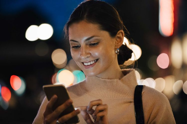 Portrait of smiling young woman using smart phone at night