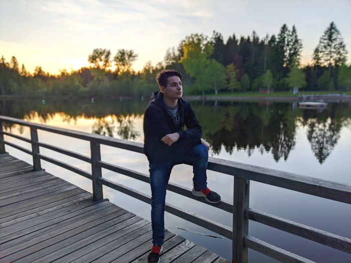 Man looking away while sitting on railing against lake