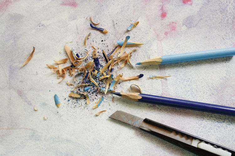 High angle view of colored pencils and shavings on table