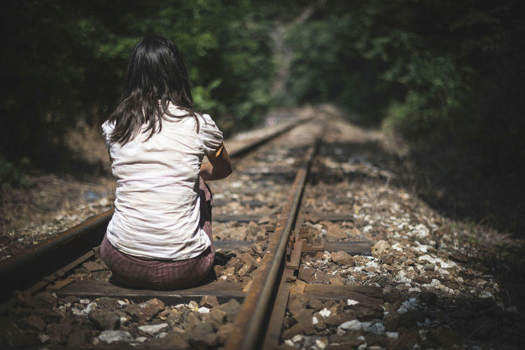 Rear view of woman sitting on railroad track