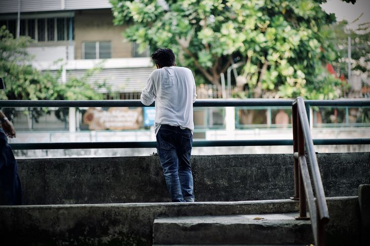 Rear view of man standing by railing