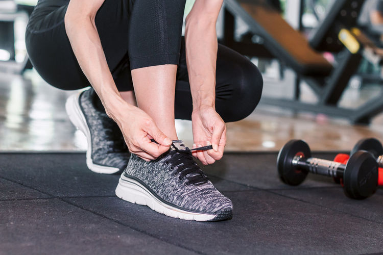 Woman tying her shoelaces with fitness equipment in the gym Adult Body Part Day Exercising Focus On Foreground Hand Healthy Lifestyle Human Body Part Human Hand Human Leg Human Limb Lifestyles Low Section One Person Real People Shoe Sport Sports Equipment Sports Training Weight Training  Women