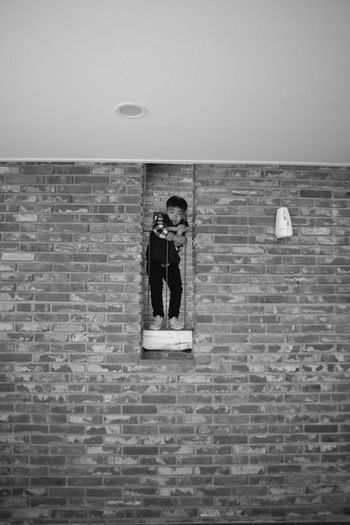 Portrait of man standing against brick wall