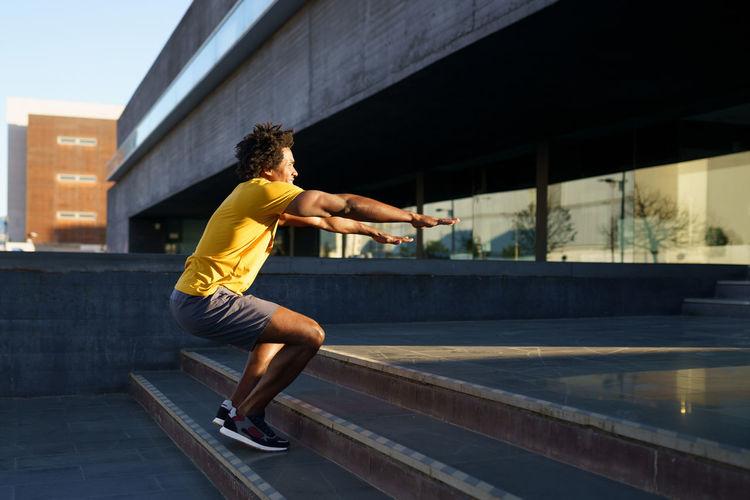 Full length of man exercising in city