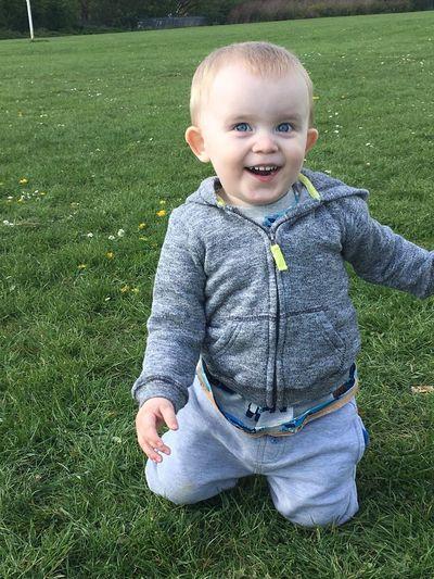 Portrait of smiling boy kneeling on lawn in city