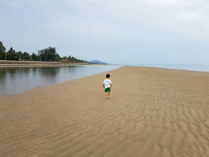 Boy walking at beach against sky