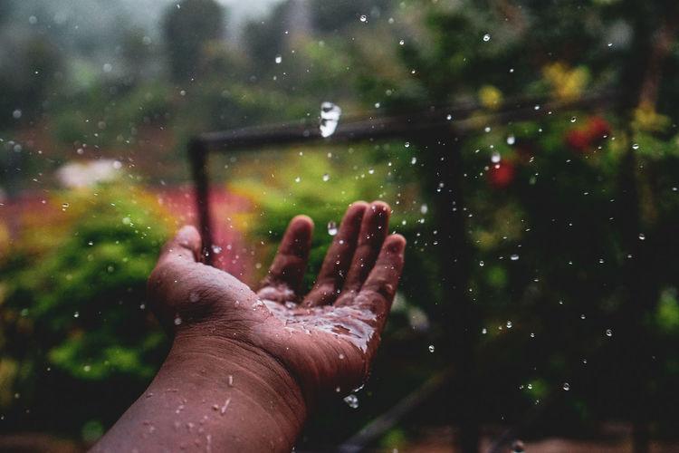 Cropped hand of man during rainy season