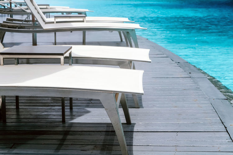 Empty chairs by swimming pool against sea