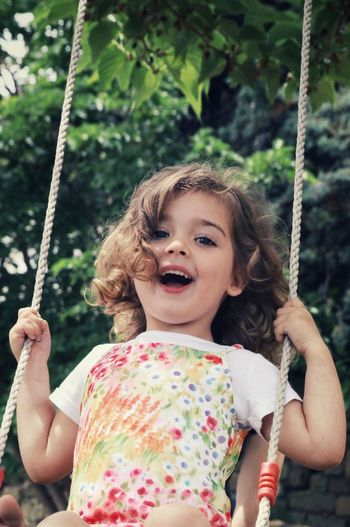 Low angle view of girl on swing at playground