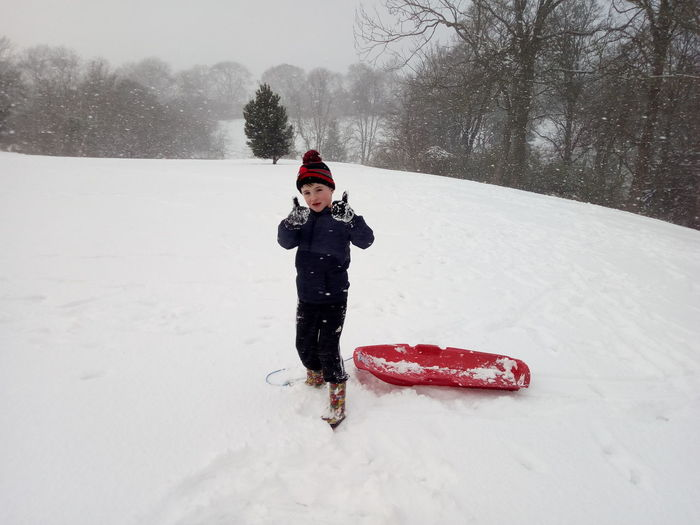 Full Length Of Boy Showing Thumbs Up On Snow Covered Field