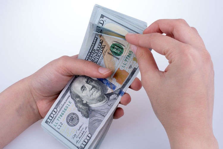 Close-up of person holding american one hundred dollar bills over white background