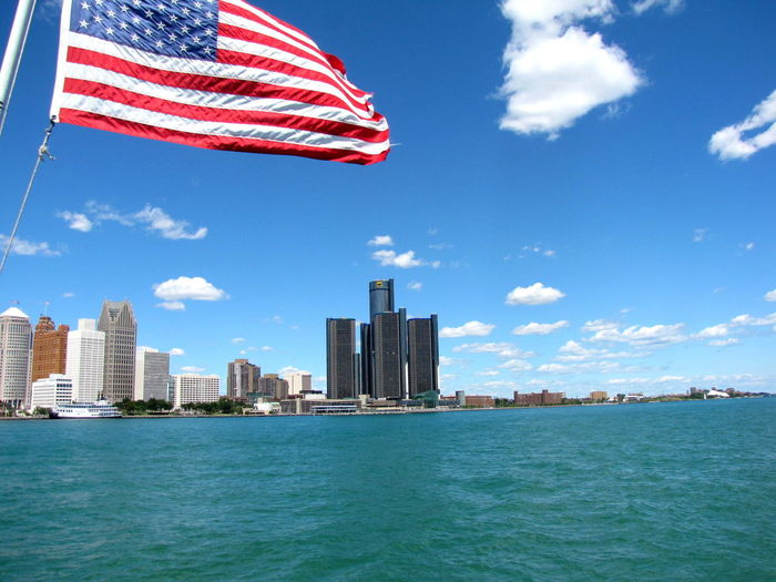 American Flag By Detroit River Against Sky In City