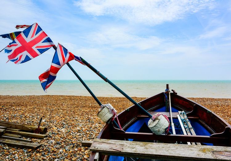 Low angle view of flags on beach against sky