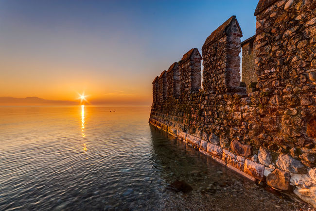 Sunrise by the Castle. Architecture Battlements Building Exterior Built Structure Calm Castle Early Garda Horizon Over Water Lake Landscape Morning Nature No People Outdoors Quiet Rays Reflection Sky Sun Sunlight Tranquility Wall Warm Water