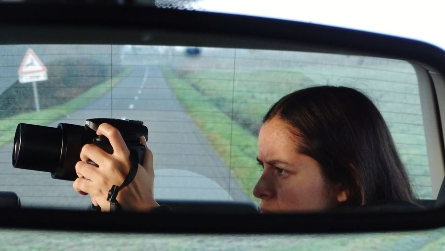 picturing Serious Concentration Concentrated Taking Photos Taking Pictures Photography Themes Technology Photographing Headshot Young Women Close-up Travel Side-view Mirror Vehicle Mirror Camera - Photographic Equipment Photographer Digital Camera Rear-view Mirror Car Interior Camera Photographic Equipment Lens - Optical Instrument Humanity Meets Technology