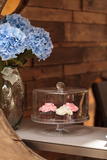 Close-up of cupcakes in cakestand by blue hydrangeas in vase on table