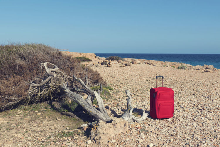 Red suitcase on a rocky sea shore at Cap de ses Salines in Majorca. Selective focus Escaping Freelance Life Holiday Light Mediterranean  Red Rocky Coastline Soft Travel Trip Vacations Wanderlust Blue Destination Journey Leisure Activity Luggage No People Packing Sea Stone Suitcase Summer Tourism Water
