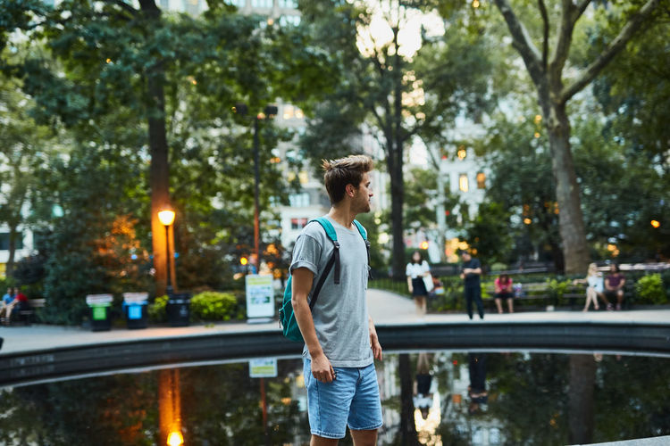 Young Man Standing By Pond In City