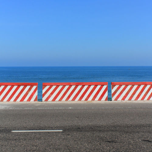 empty road , ocean and blue sky Beauty In Nature Blue Blue Sky Clear Sky Day Empty Empty Places Empty Road Highway Horizon Horizon Over Water Nature No People Ocean Outdoors Red Scenics Sea Simple Sky The Way Forward Tranquil Scene Tranquility White