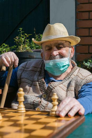 Senior man playing chess in yard