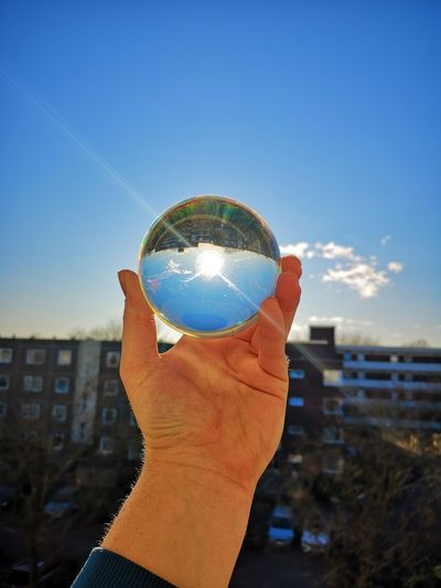 Cropped hand holding crystal ball against blue sky during sunny day
