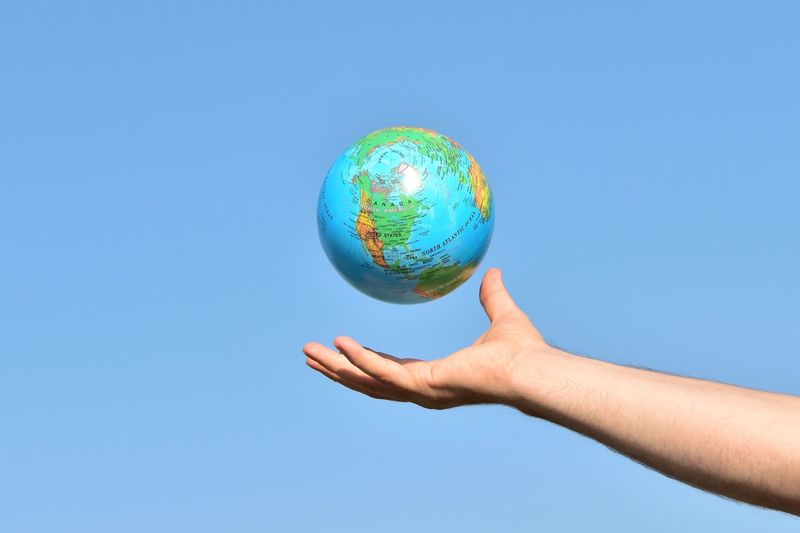 Cropped hand of man reaching globe against clear blue sky