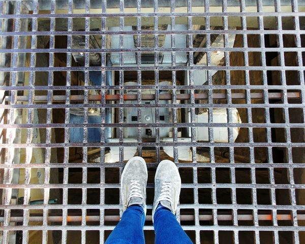 Vertigo Metal Grate One Person Personal Perspective Human Leg Prison Metal Outdoors One Man Only Day Highness High Florence Italy Shoes Jeans Gates