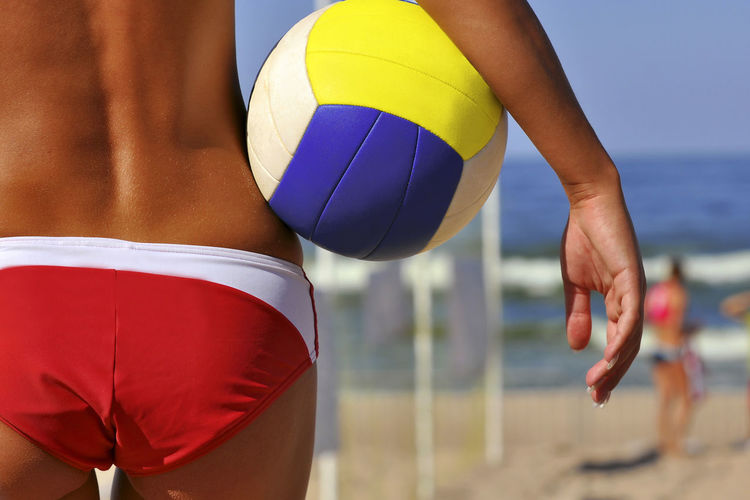 Rear view midsection of woman holding volleyball at beach