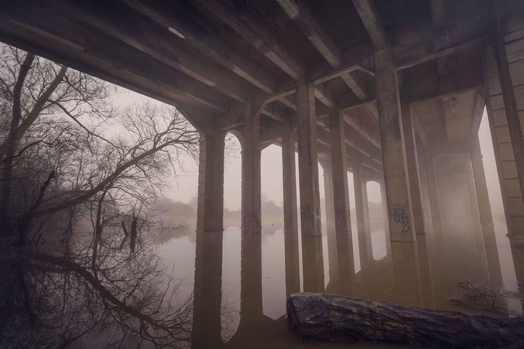 Bridge on calm lake in foggy weather