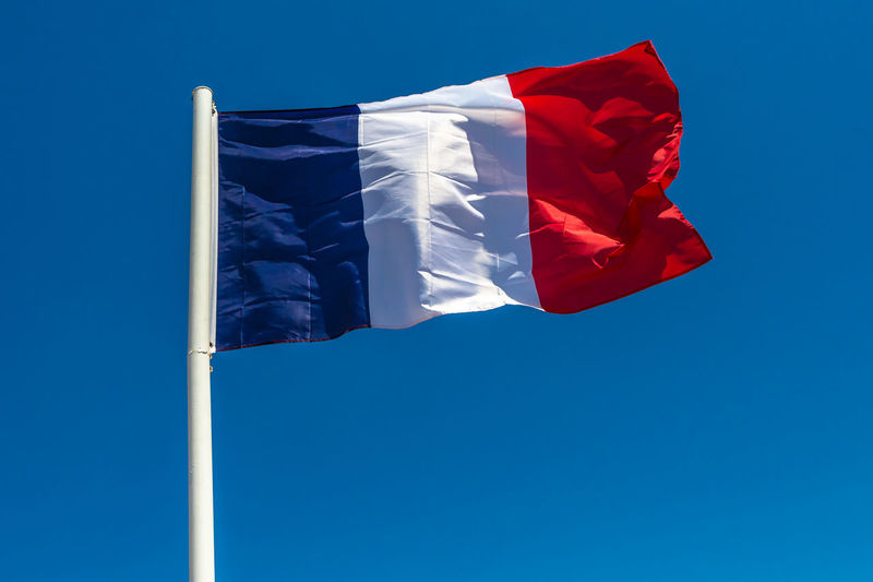 Low angle view of french flag waving against clear blue sky