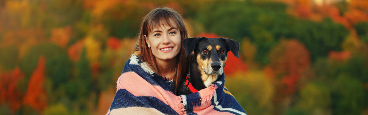 Portrait of smiling young woman with dog against blurred background