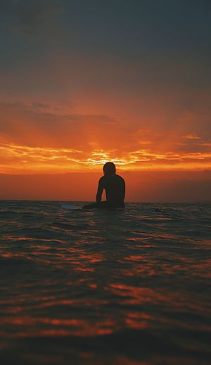 Silhouette Of Man In Sea Against Sunset Sky