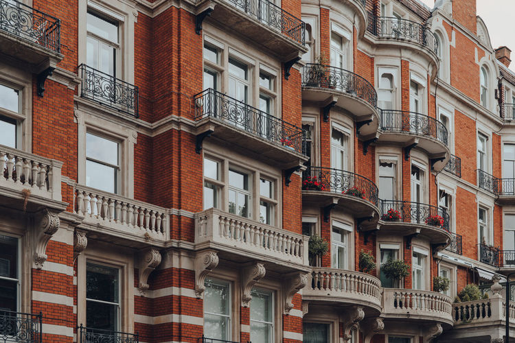 Exterior of a traditional red brick apartment block with balconies in kensington, london, uk.