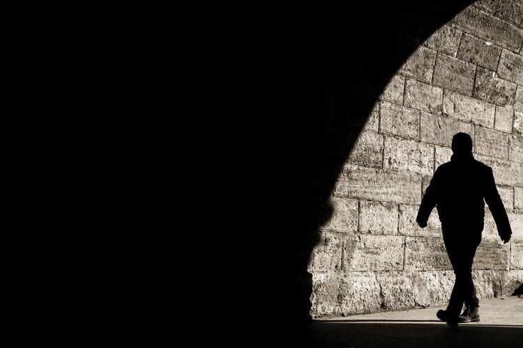 Rear view of silhouette man walking on footpath