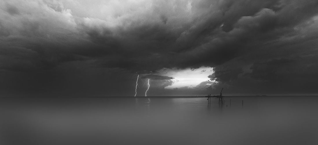 A stormy scene was captured in monochrome. Beauty In Nature Cloud - Sky Day Forked Lightning Horizon Over Water Lightning Nature No People Outdoors Power In Nature Scenics Sea Sky Sky, Storm, Stormy, Light, Lightning, Nature, Power, Strike, Dark, Blue, Weather, Thunderstorm, Striking, Thunder, Dramatic, Bright, Cloud, Electric, Energy, Danger, Bolt, Electricity, Rain, Night, Background, Flash, Thunderbolt, Extreme, Shock, Overcast, Storm Cloud Thunderstorm Tranquility Water Waterfront Weather