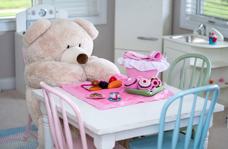 A life sized stuffed bear has a pretend picnic in a child's playroom Stuffed Toy Teddy Bear Picnic Animal Representation Art And Craft Chair Childhood Comical Crib Day Giant Bear Home Interior Indoors  Life Size  Pink Color Playroom Representation Seat Softness Still Life Stuffed Toy Table And Chairs Teddy Bear Toy Toy Animal Toy Food