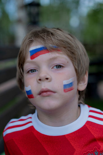 Little boy football fan with makeup on his face in the form of the Russian flag and a red t-shirt with the emblem of Russia. Football Football World Cup Russia Casual Clothing Child Childhood Close-up Day Emblem  Flag Flags Focus On Foreground Front View Headshot Human Face Innocence Looking At Camera Males  One Person Patriotism Portrait Real People Red Striped