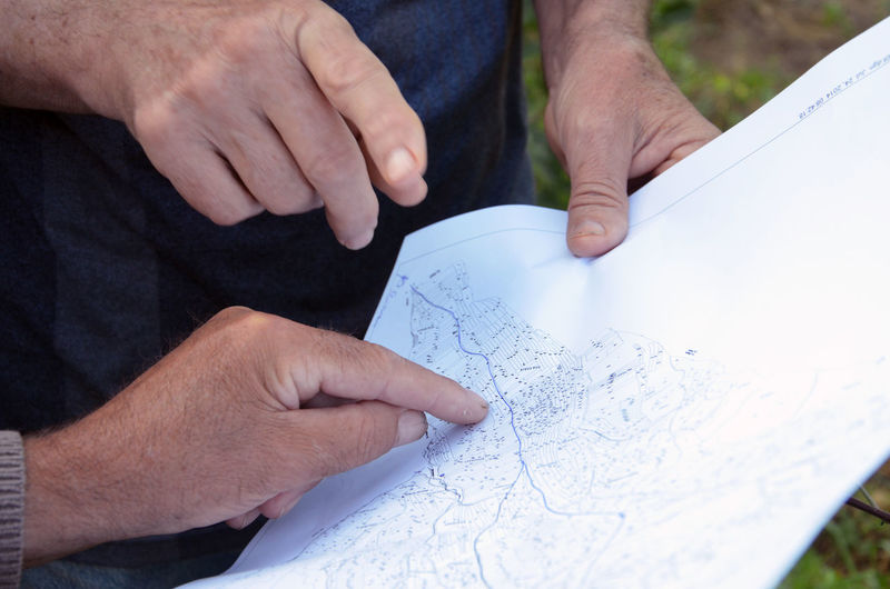 Cropped image of people discussing over map outdoors