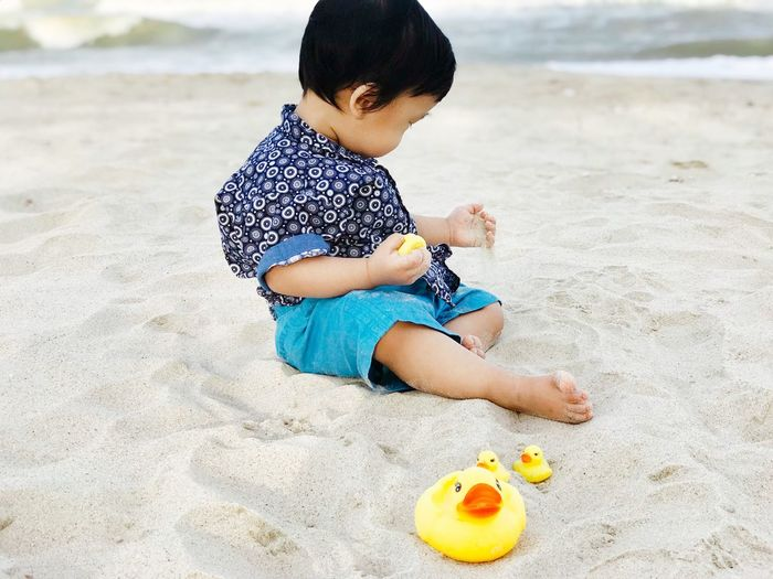 Boy playing with toy on sand at beach