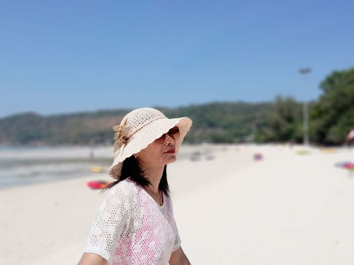 Woman wearing hat standing at beach against clear blue sky