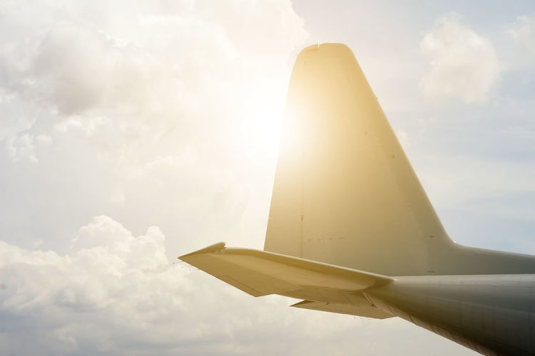 Low angle view of airplane flying against sky on sunny day